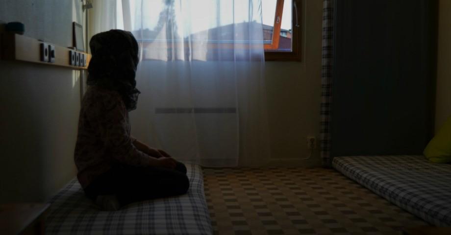 Syskonen sover på madrasser i ett hotellrum.