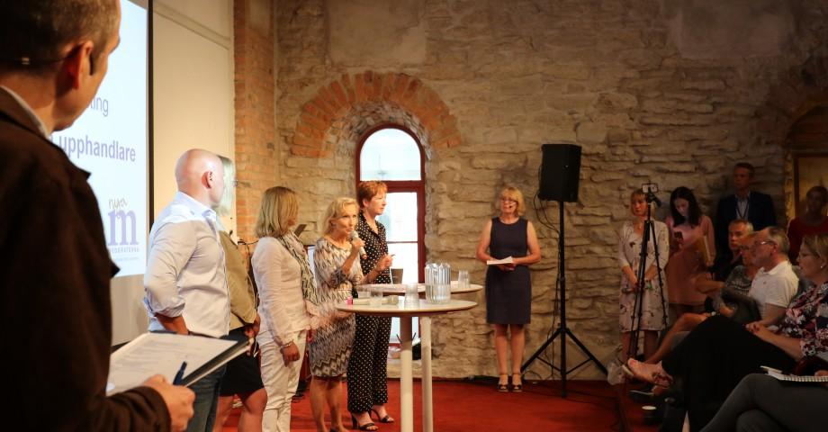 Seminarium om upphandling. Irene Svenonius (M) står vid högtalaren vid väggen. Bild: Moderaterna.