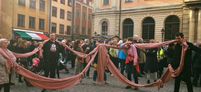 Kampanjorganisationen Skiftet bildade en jätterosett under manifestationen på Stortorget. Bild: Skiftet.