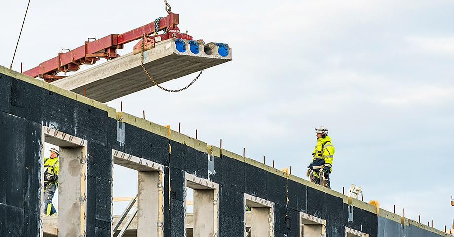Byggnadsarbetare på taket till ett hus