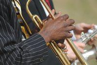 Detaljbild på två män som spelar trumpet och saxofon