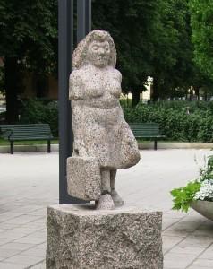 """Skultpuren """"Husmorssemester"""" av Olof Thorwald Ohlsson (1973) föreställer en kvinna med resväska och står i Tessinparken i Stockholm."""