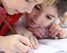Två barn i en skolbänk som skriver i ett block