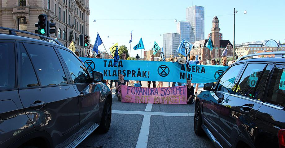 Två bilar som står stilla framför aktivister från Extionction Rebellion som blockerar vägen med banderoller. Banderollerna har texterna Förändra systemet inte klimatet och Tala klarspråk!