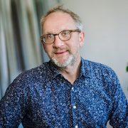 Porträttbild på Jan Bergdahl i en blommig blå skjorta och glasögon