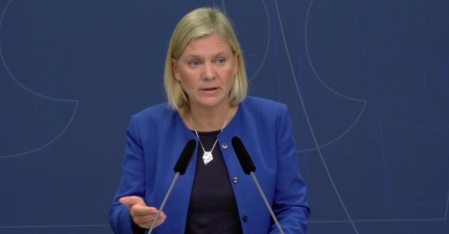 Magdalena Andersson står vid ett podium och talar.
