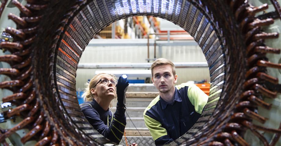 Produktingenjör och maskintekniker lyser med ficklampa för att inspektera en stator.