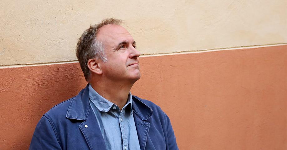 Porträtt av Thord Eriksson framför röd och gul putsvägg. Han har blå skjorta och blå jacka.