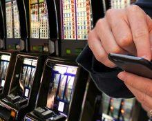 BIld på enarmade banditer på rad i ett casino och en infälld bild av manshänder som spelar på en mobiltelefon
