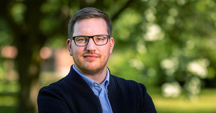 Porträttbild på Håkan Svenneling med en allvarlig min. Han str utomhus och har armarna i kors.