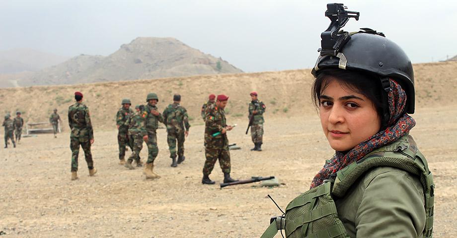 En bild på journalisten Najwa Alimi i kamouflage-kläder och en skyddshjälm som har en kamera fäst ovanpå. Hon tittar rakt in i kameran och i bakgrunden syns afghanska militärer.