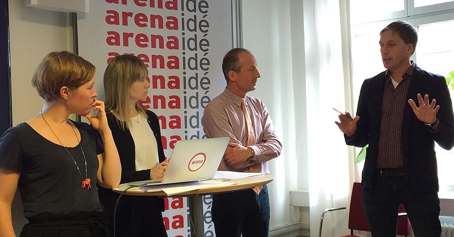 Bild på de fyra deltagarna inbegripna i samtal under seminariet. Christer Gerdes från Riksrevisionen talar och gestikulerar. I bakgrunden syns Arena Idés logotyp på en vepa.