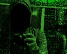 En grönfärgad bild på en person vars ansikte är dolt i skuggan under en huvtröja - och med en kamera i händerna