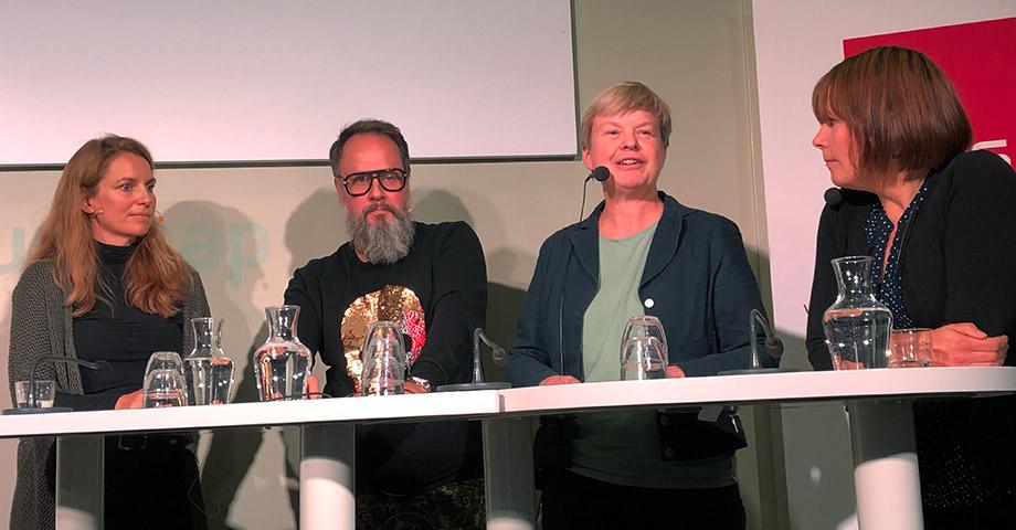 Bild på expertpanelen vid ett vitt bord. Åsa Domeij talar i mikrofon.