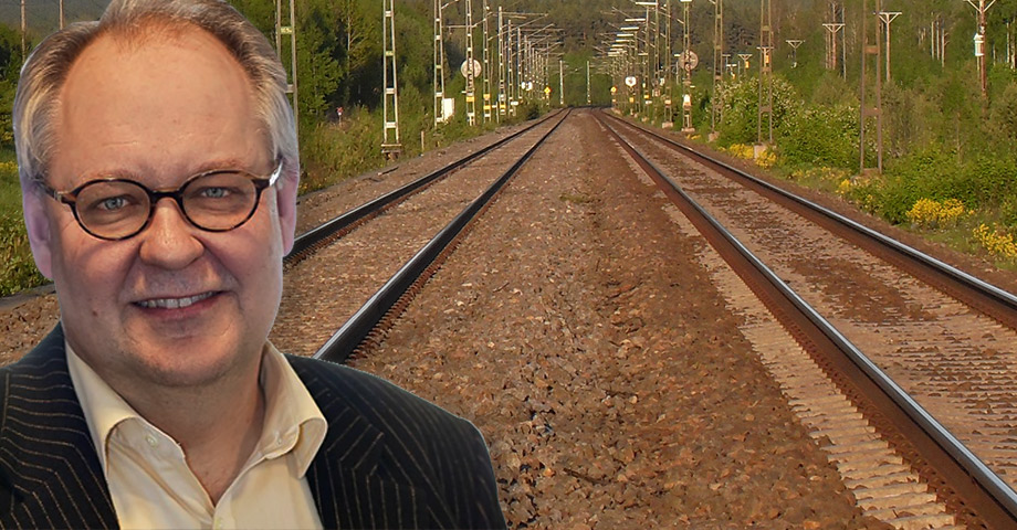 Porträttbild på krönikören Anders Jonsson infälld i en bild som visar två järnvägsspår av stambanan