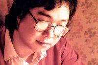En porträttbild på Gui Minhai som sitter och skriver