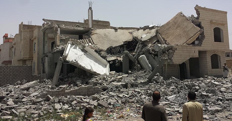 Ruinerna efter ett utbombat hus, med två vuxna och ett barn som står i förgrunden