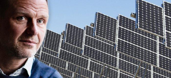 Porträttbild på Jonas Nordling, infälld i en bild på flera rader av solceller på stålställningar