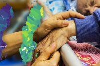 En närbild på en äldre människas hand som en vårdpersonal håller i, en äldre man i en sjukhussäng skymtar i bakgrunden