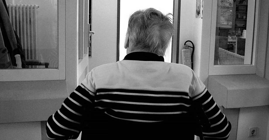 En äldre man i rullstol som sitter med ryggen mot kameran