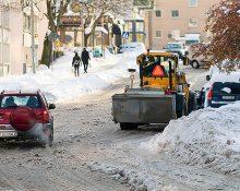 En plog i ett tättbebyggt område med både en bil och gående på trottoar